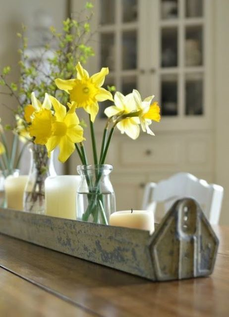 a galvanized long planter with candles, jars and vases and daffodils and blooming branches as a rustic spring centerpiece