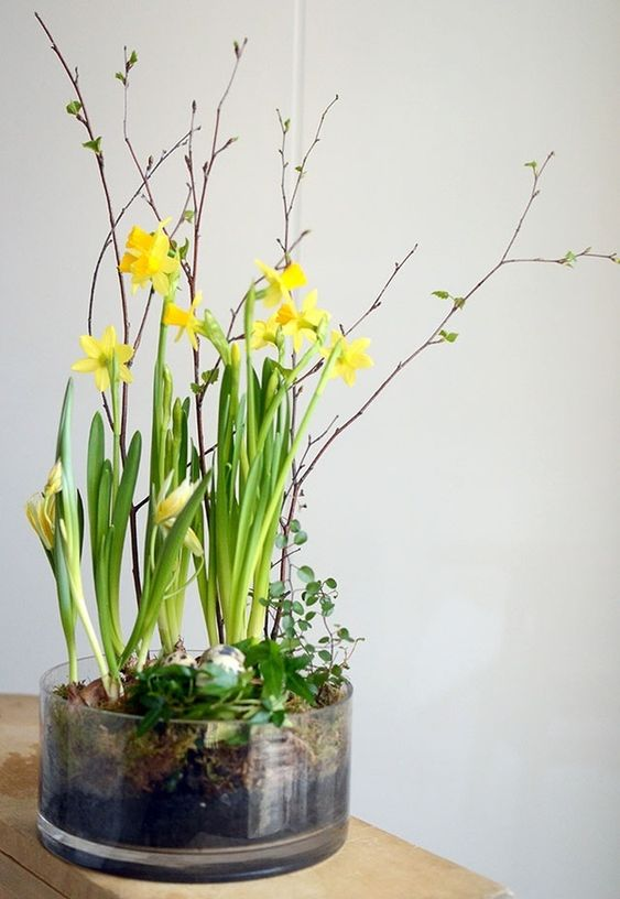 a glass bowl with fake eggs and greenery, daffodils and blooming branches is a modern and chic spring centerpiece