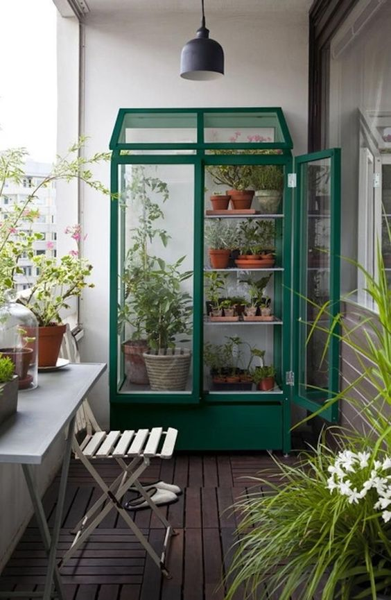 a green greenhouse with lots of potted plants and more plants around it for a spring look