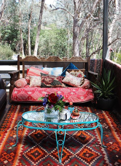 a gypsy-styled porch with a bright printed rug, a colorful bench and a blue forged side table