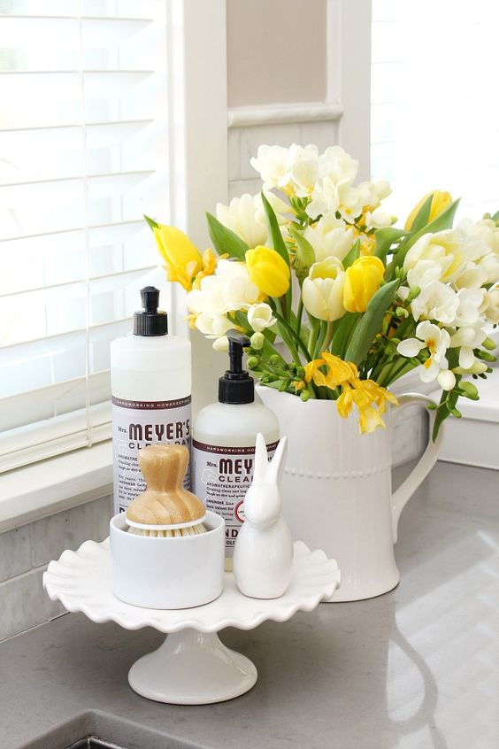 a jug with white and yellow blooms is a nice spring arrangement for kitchen decor