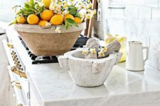 a large bowl with lemons and white blooms is a bold and cool idea for spring kitchen decor