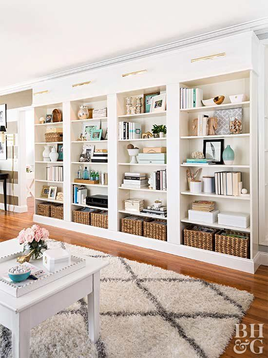 a large built in bookshelf unit with lots of books, vases, baskets and candles is a cool idea for a home office