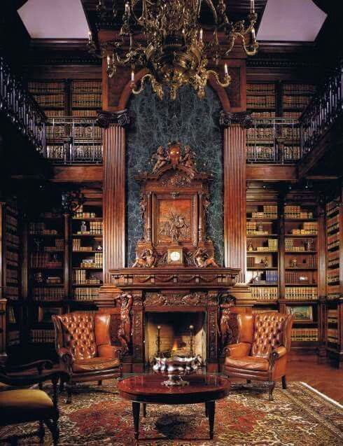 a large exquisite Gothic library with bookshelves covering all the walls up to the ceiling, a fireplace wiht a carved mantel, leather chairs and a refined chandelier