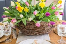 a large nest with bright tulips and daffodils, moss with bunnies and wicker chargers for a spring table