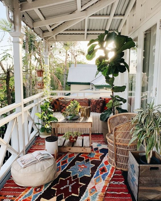 a lovely boho porch with wooden and woven furniture, colorful printed textiles, potted plants and greenery, layered rugs