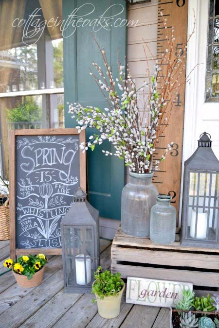 a lovely spring porch with a chalkboard sign, candle lanterns, churns with willow pussy and bright blooms