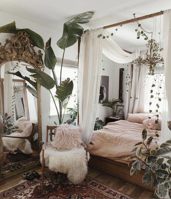 a messy boho spring bedroom with wooden furniture, pink bedding, a boho rug and lots of greenery and plants