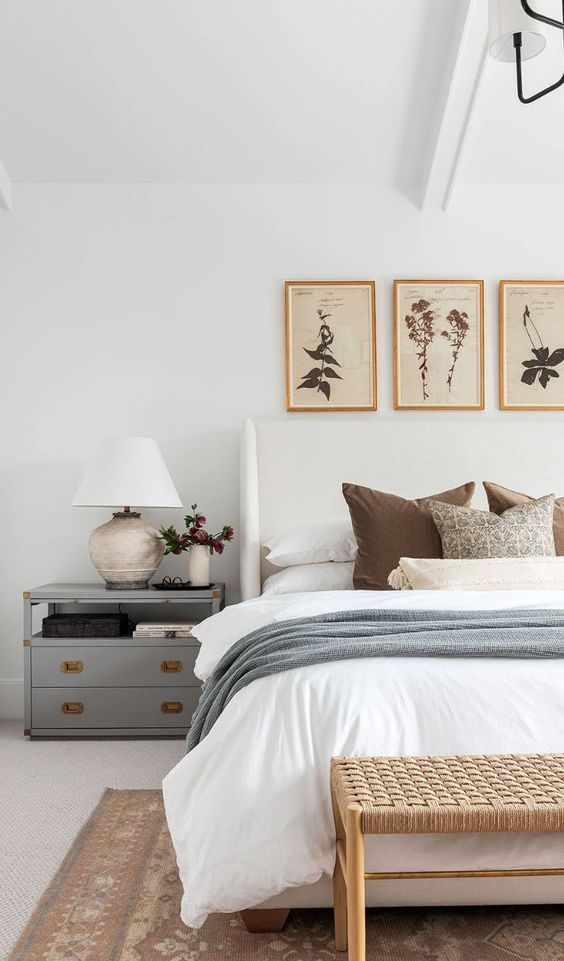 a mid-century modern bedroom with a grey nightstand, a woven bench, a white bed, grey and white bedding