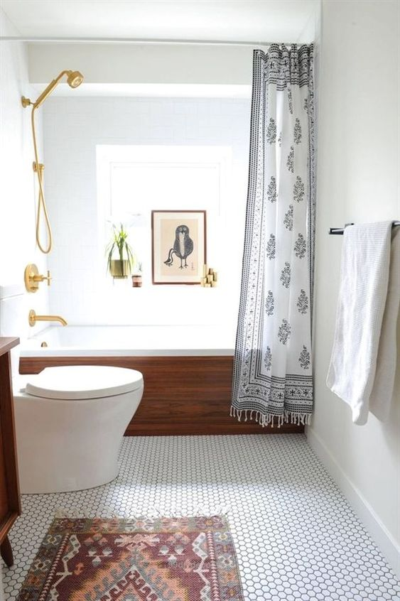 a modern small bathroom with a penny tile floor, a wood clad bathtub, a rug, an artwork and gilded touches