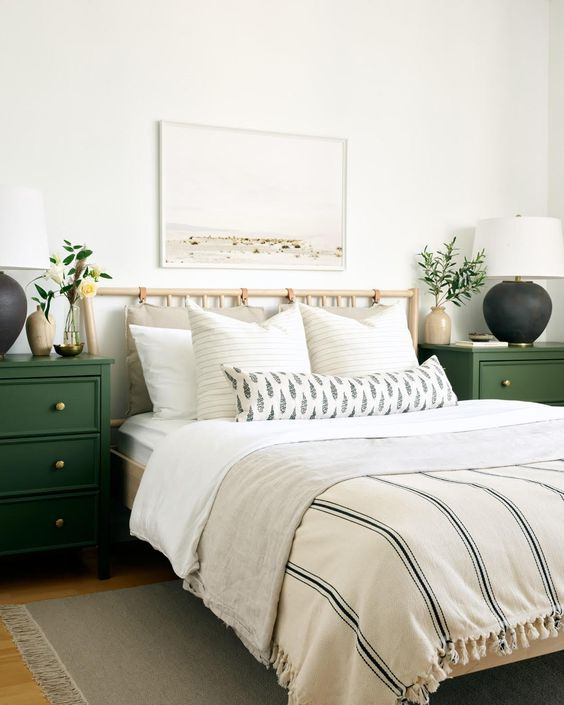 a modern spring bedroom with green nightstands, printed bedding, a neutral artwork and greenery
