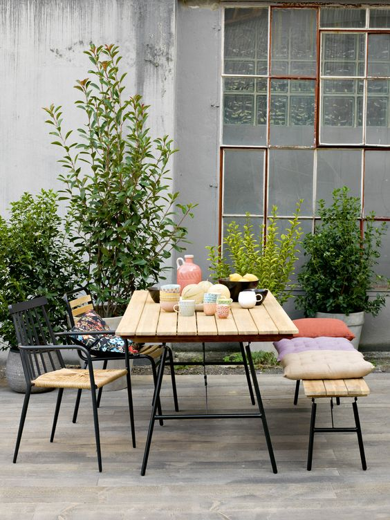 a modern spring terrace with a simple and chic dining set, potted greenery and bright pillows is a fun and cool idea
