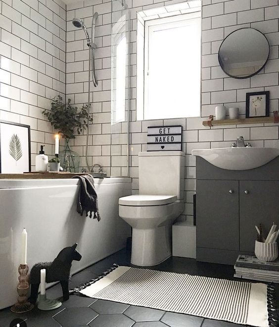 a monochromatic bathroom with a hex tile floor, subway tiles on the walls, a tub, candles and some cute decor