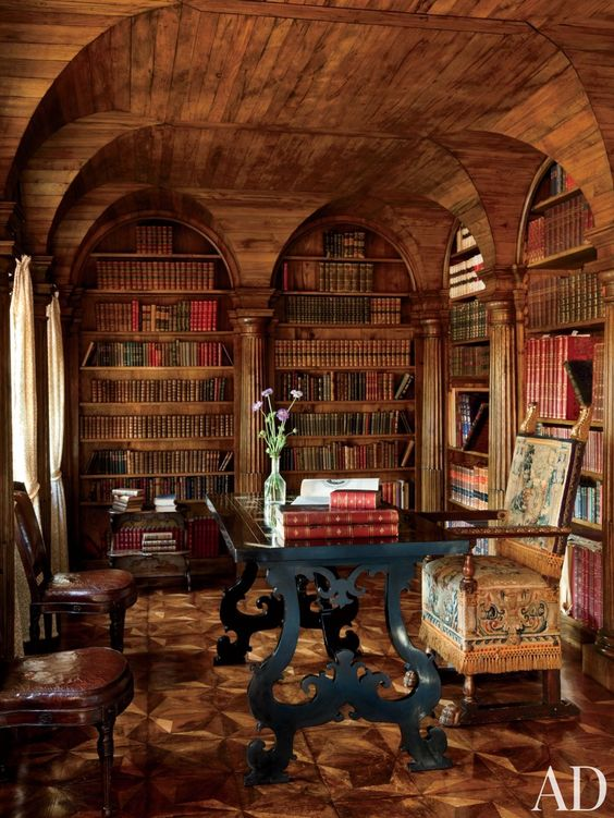 a moody Gothic library and home office with an arched ceiling, a black carved desk, heavy chairs is a beautiful example of Gothic style