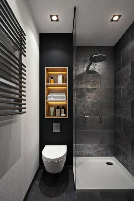 a moody black bathroom with stone-inspired tiles, a wall shelf with lights, a shower space