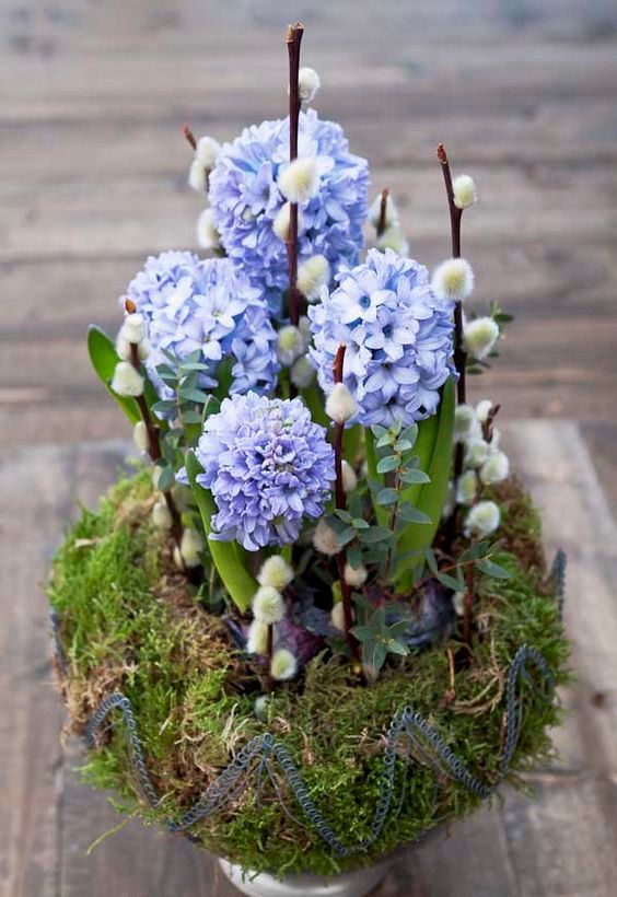 a moss ball with willow, blue hyacinths and greenery is a creative spring decoration for indoors and outdoors