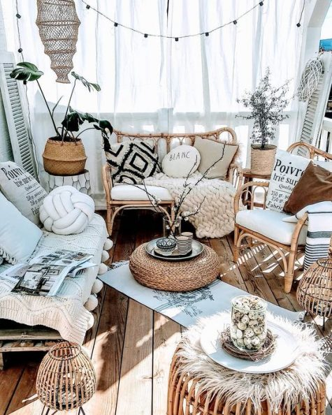 a neutral boho porch with rattan furniture and candle lanterns, lights, potted plants, pillows and textiles