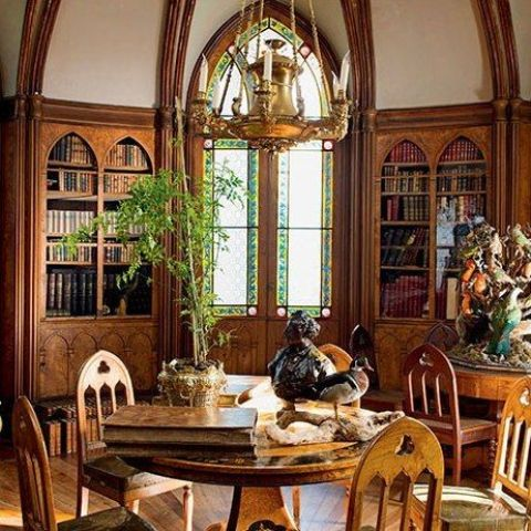 a neutral-colored Gothic home library with arched mosaic windows, arched built-in bookcases, round tables and refined chairs plus a gilded chandelier