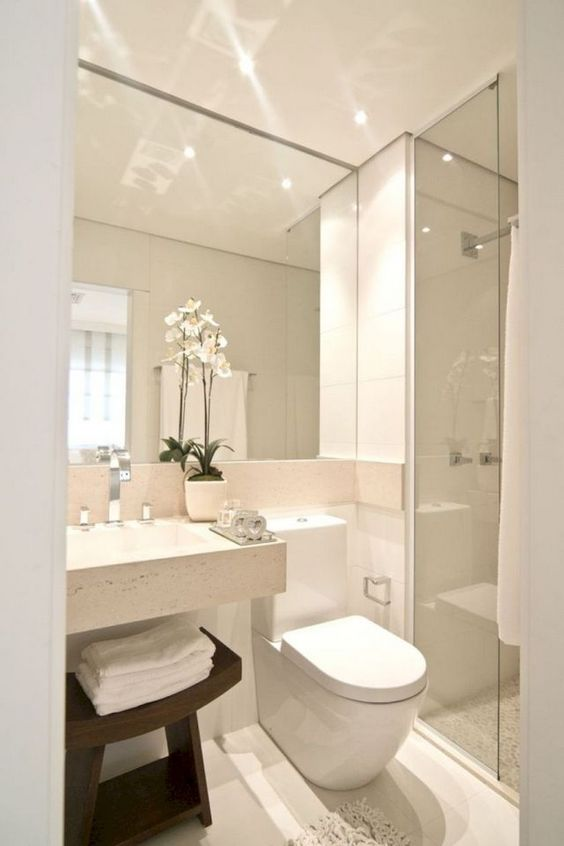 a neutral minimalist bathroom with a large mirror, a square sink, a shower space and a dark stained wooden stool