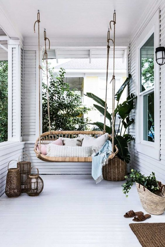 a neutral tropical boho porch with a rattan hanging seat, potted greenery, candle lanterns and jute rugs