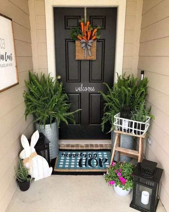 a plaque bunny, candle lanterns, potted ferns, a fake carrot door decoration and a bright printed rug