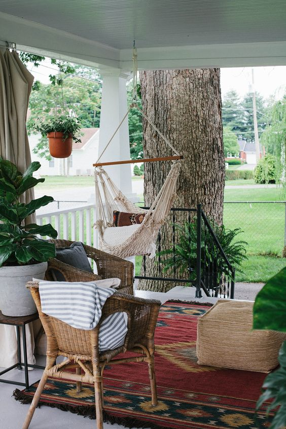 a relaxed boho porch with woven furniture, a hanging macrame chair, boho rugs and potted greenery