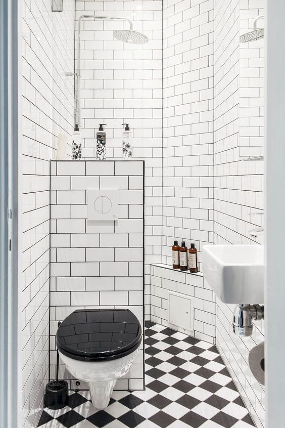 a retro-inspired black and white bathroom with a shower space, a mosaic tile floor and a half wall