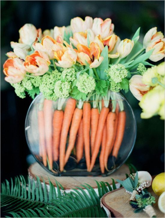 a round aquarium with frehs carrots and matching orange tulips is a bold spring or Easter decoration