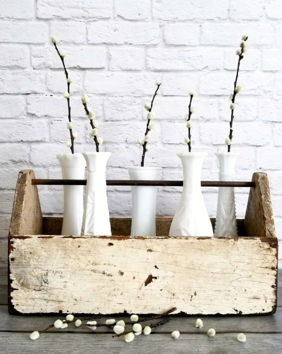 a rustic spring decoration of a tool box with white vases and willow will brign a cozy feel to your home