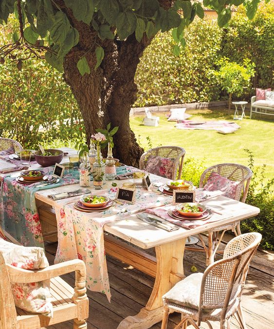 a rustic spring terrace with a wooden table and wicker chairs, with floral runners and napkins set for a party