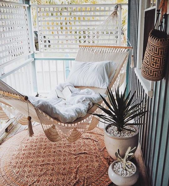 a screened boho porch with a macrame hammock with neutral linens, a printed rug, potted plants is a cool space