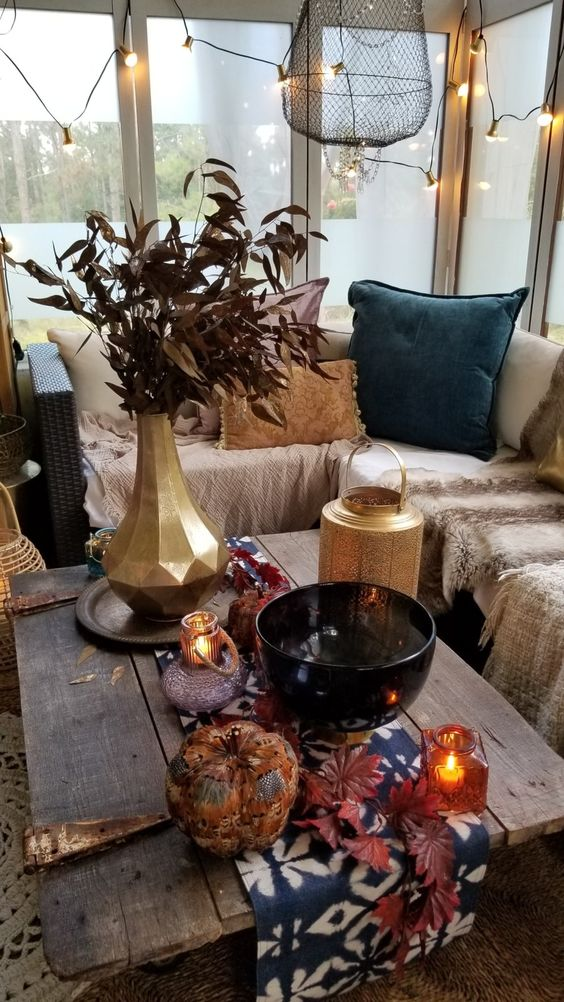a screened boho porch with a sectional with neutral layered textiles, colorful fall table styling, touches of gold and lights