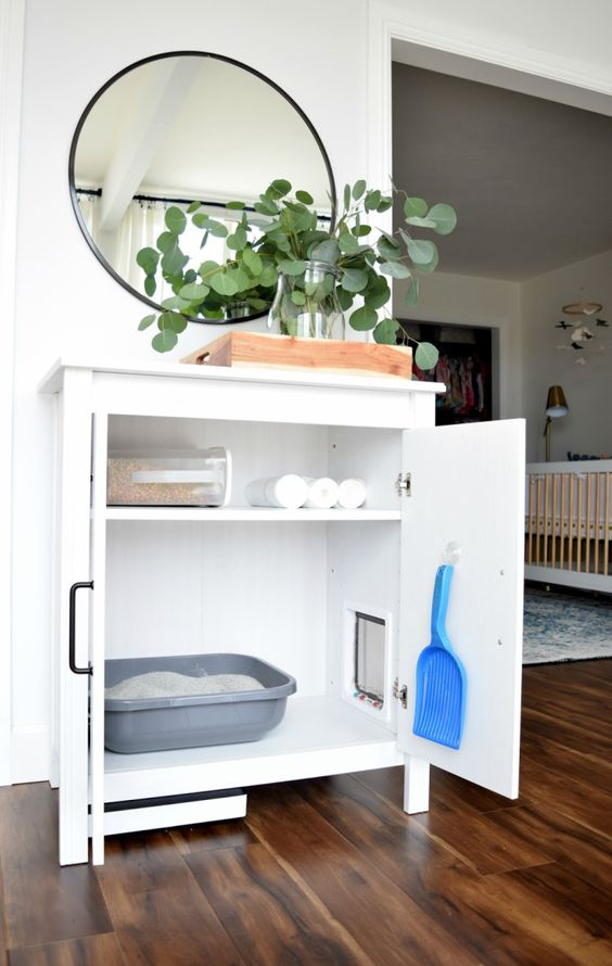 a simple and neutral white cabinet with a cat litter box inside and everything necessary inside it, too
