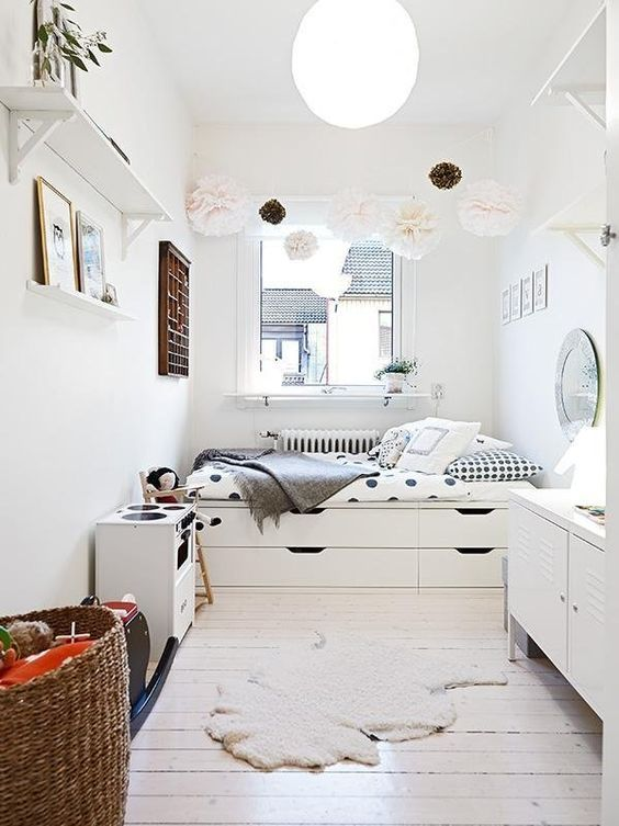 a small Nordic bedroom with a storage bed, a pompom garland, storage units and open shelves