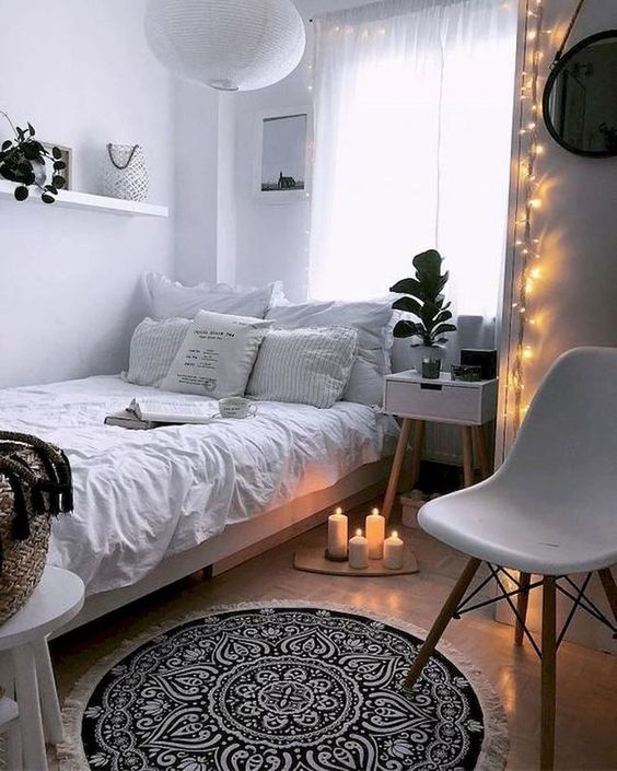 a small Scandinavian bedroom with white walls and furniture, lights, candles and pendant lamps