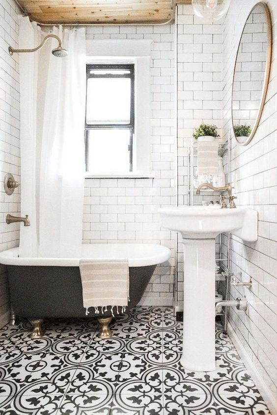 a small and bright bathroom with a mosaic floor, a wooden ceiling, a black clawfoot tub and a free-standing sink