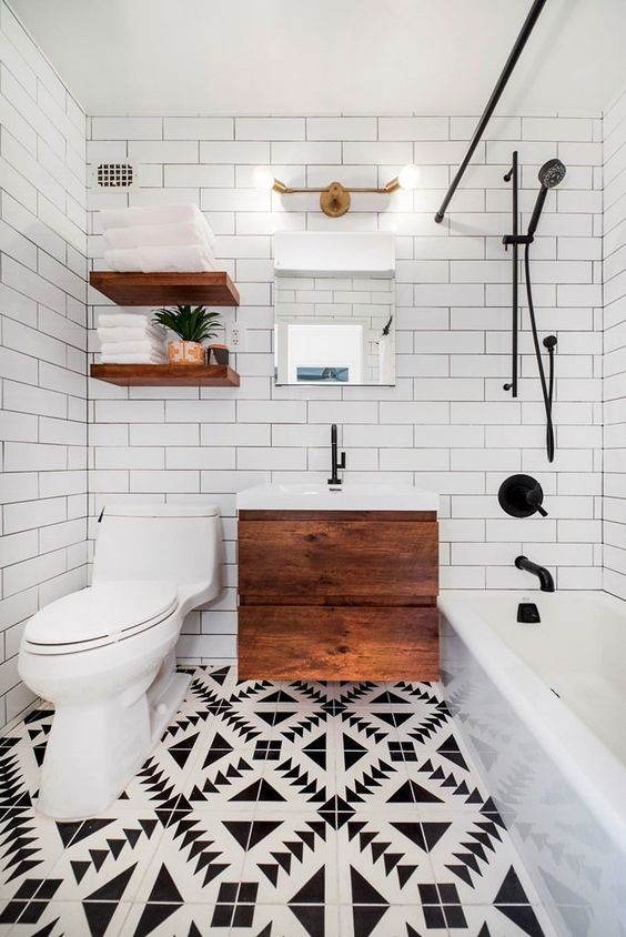 a small and chic modern bathroom with a mosaic floor, a floating wooden vanity, open shelves, a tub and white subway tiles