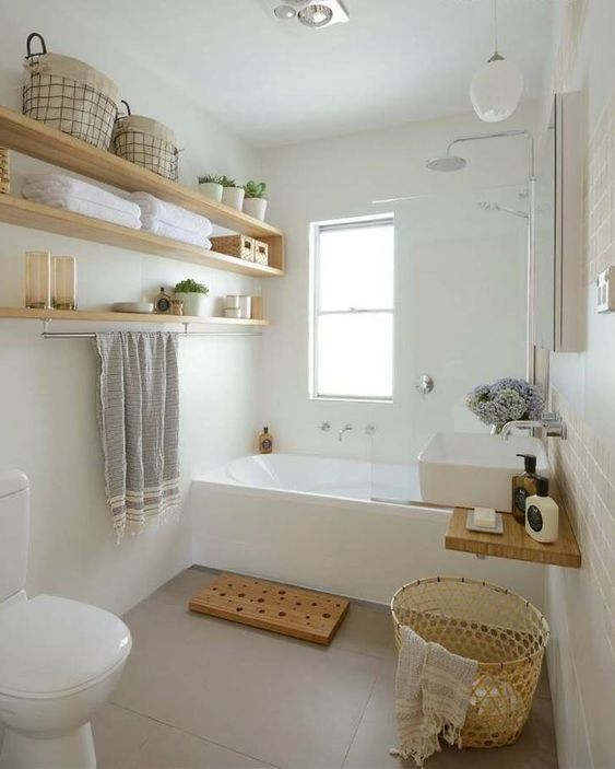 a small and serene bathroom with a tub, open shelves, a sink, wicker and wooden touches here and there