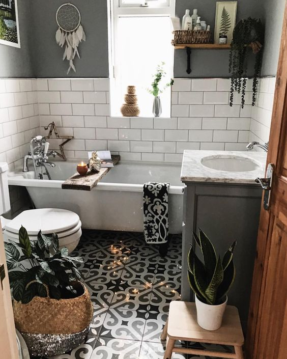 a small boho bathroom with a mosaic tile floor, grey and white tile walls, a tub, potted greenery and baskets for storage