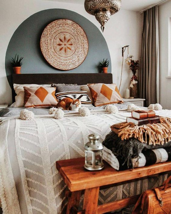 a small boho bedroom with a black bed, a Moroccan lamp, a wooden bench and potted plants here and there