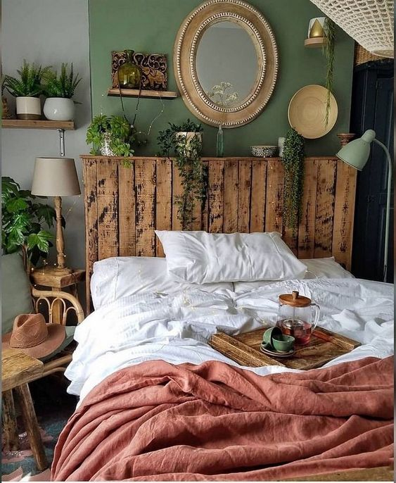 a small boho bedroom with a green wall, a pallet bed, a gallery wall, some lamps and potted greenery and catchy textiles