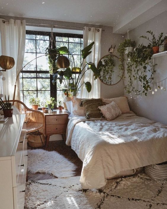 a small boho bedroom with cascading greenery in pots, wooden furniture and brass lamps