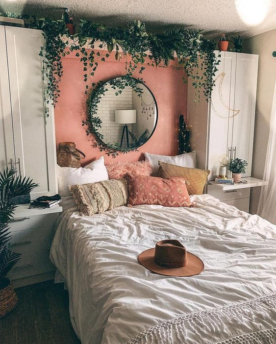 a small boho bedroom with white wardrobes and a built-in bed, lots of cascading greenery, boho pillows and lights