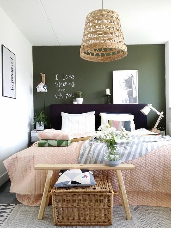 a small catchy bedroom with a green accent wall, a black bed, a wicker lamp and chest and printed textiles
