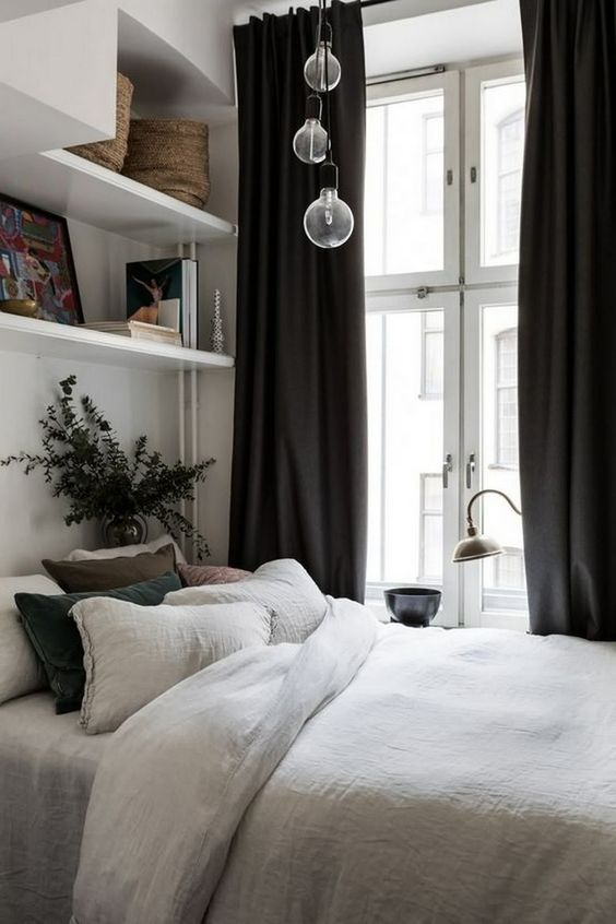 a small chic bedroom with open and closed shelves, a bed with cool bedding, pedant lamps and black curtains