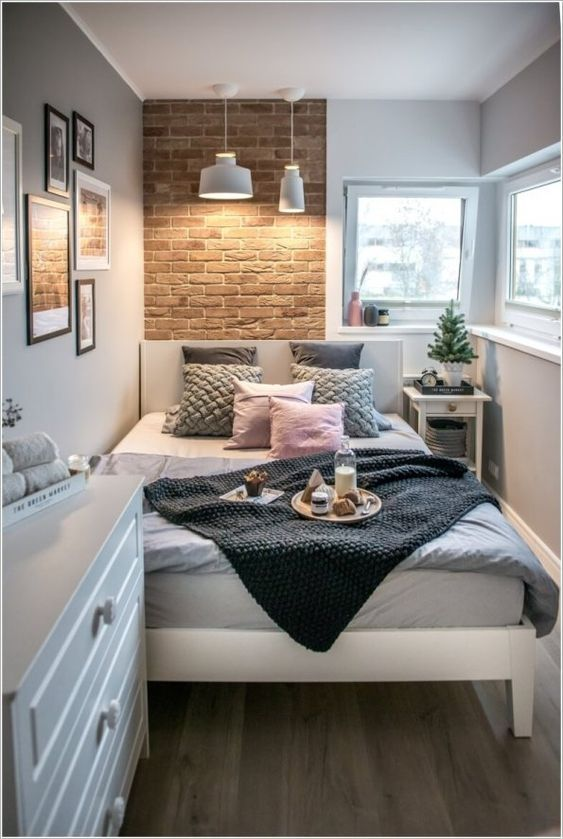 a small contemporary bedroom with a brick wall, a white bed and dresser, pendant lamps and catchy bedding