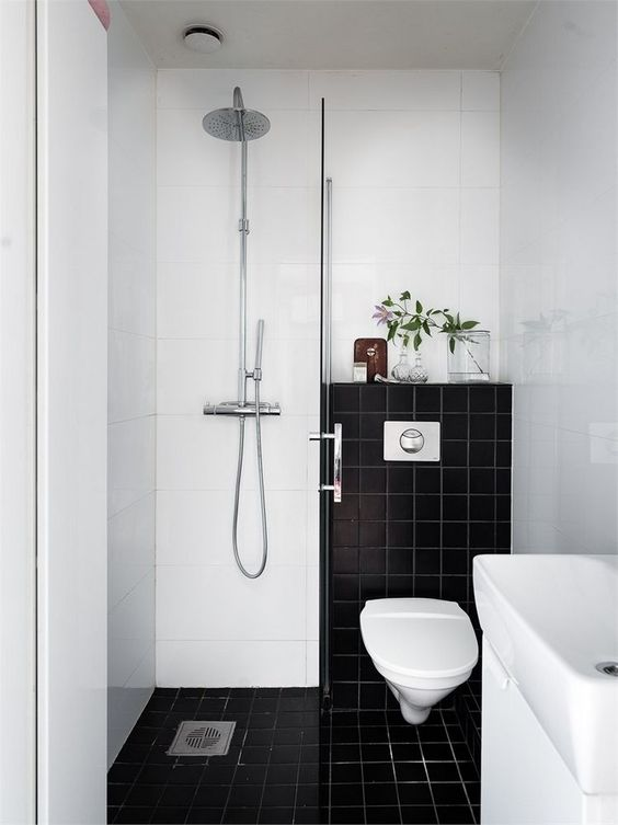a small contrasting bathroom with black and white tiles, a shower space, a sink and greenery to refresh the look