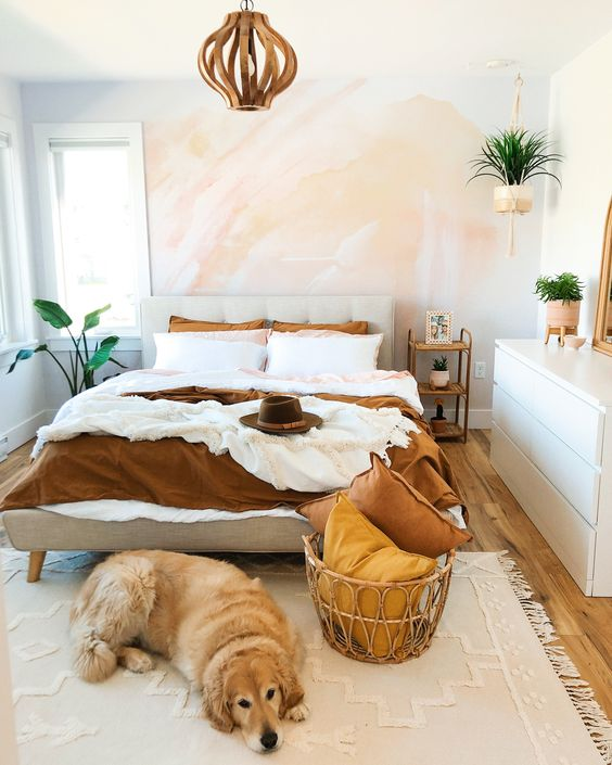 a small modern bedroom with a watercolor wall, a sleek white dresser, an upholstered bed and a wooden lamp, potted plants