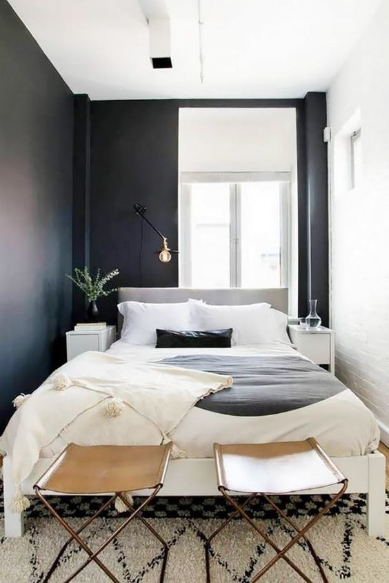a small modern bedroom with black and white walls, a grey bed, leather stools and lamps and bulbs