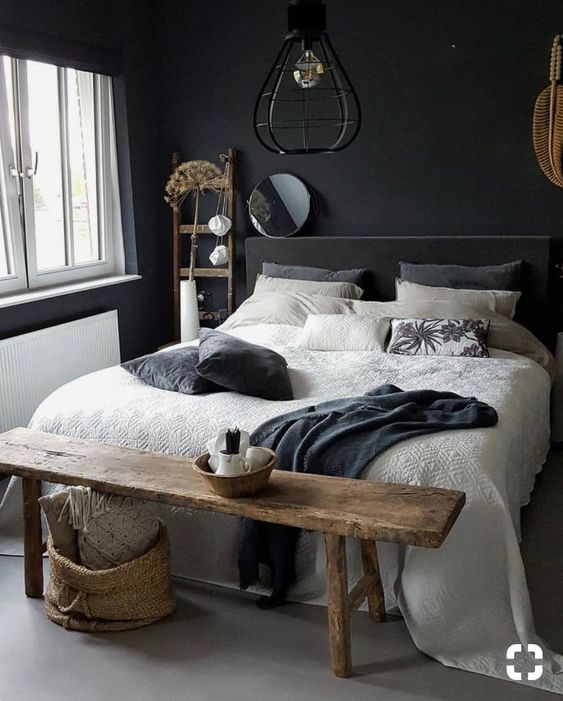 a small moody bedroom with black walls and a bed, with a wooden bench and ladder, pendant lamps